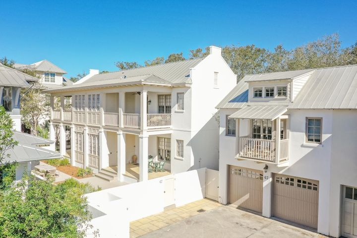 South of Scenic 30-A in the community of Rosemary Beach, this newly renovated Charleston courtyard home proudly sits on a quiet cul-de-sac. Protected by a white stucco perimeter wall, this wide parcel opens directly onto serene Boardwalk E.Artfully designed by Looney Ricks Kiss, 67 Dunmore Town Lane is graced by majestic parapets and an abundance of private spacious porches. It offers a wonderfully crafted floor plan on two levels providing easy living for families and their guests. An abundance of large windows and spacious porches grace this stunning 5 bedroom, 5 1/2 bath that includes a separate carriage house residence.Newly custom furnished in a Rustic Modern style with a coastal flair featuring clean lines of whites, grays, and beiges.