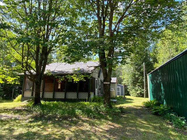 Cordwood construction cottage with many recent updates on Lost Lake Rd. Quiet 1.5-acre lot