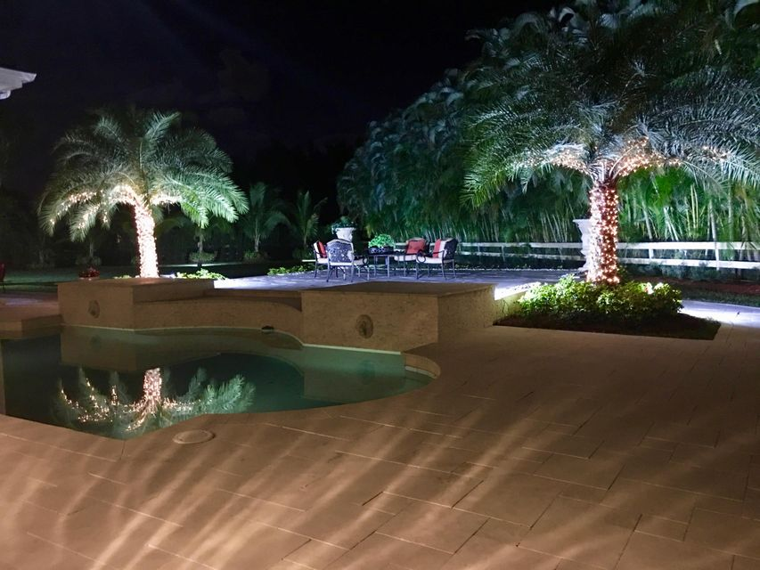 night photo of pool, sitting area and ar