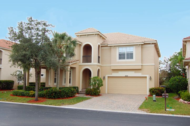 Elegant home with paver driveway with wrap around porch and 2nd floor balcony.