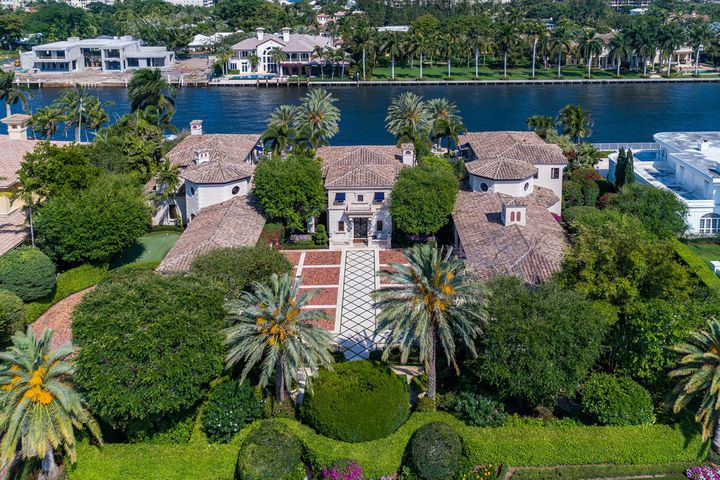 This Royal Palm Yacht & Country Club private estate built by Brennan Custom Homes is situated on 200' of the Intracoastal waterway. From the moment one enters the gated motor court driveway entry surrounded by stunning manicured landscaping affording great privacy, its distinguished presence offers an impeccable stage for elegant entertaining and intimate daily life.The detail and superb craftsmanship of this estate goes unsurpassed. The home has over 11,000 sq. ft. of air conditioned living space with a separate guest house.  There are a total of six bedrooms, nine full and three half baths. From the moment, you enter the grand rotunda foyer with hand painted ceiling detail and marble stone sculptures, you will have a vast view through the great room with wood flooring, gas fireplace with onyx and stone mantle, hand painted walls, wood ceiling with hand painted gold foiling leading out through French doors to the cover loggia area overlooking the Intracoastal waterway. Many of the other interior features consist of gallery hallways with custom designed  detail leading to the formal dining room, temperature controlled wine cellar with a wine tasting room, its oversized eat-in gourmet kitchen is sleek and well equipped with wood cabinetry, solid stone countertops, including a large center island which is well located near the family room and billiard's room, top-of-the-line appliances, two story library/office with hand carved wooden doors, custom built-ins and fireplace lead out to a private garden oath and putting green, elevator, exercise room with a full bath and steam shower, a separate private master suite has his/her baths and large walk-in closet, wood flooring, breakfast bar and a private loggia with fireplace overlooking the Intracoastal waterway. The separate guest house features two bedrooms and two baths, sitting room with wet bar, plantation shutters and a private patio area with a garage.  Extensive millwork with an unrivaled level of detail, custom built-ins & elaborate moldings. The interior is grand, yet warm & welcoming to all who enter. The exterior highlights of the property consist of a fanciful koi pond, large pool with hot tub, a full summer kitchen with two pizza ovens, custom tiling and bar seating, 10 air conditioning units and a brick/concrete driveway with a large water feature and a five-car garage.    Call Listing Company for a floorplan, and more details. Private showings only! Contact Listing Company today!