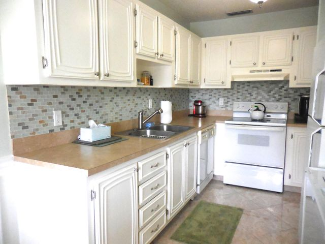 updated kitchen with cabinets, backsplash, counters