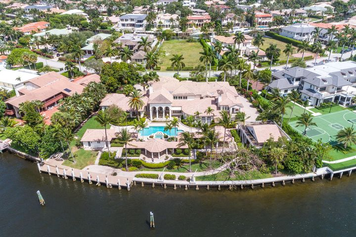 This estate home is situated on a double lot with 248 feet of direct Intracoastal and canal water frontage. Front entry to the property includes a front motor court and port cochere. The interior features a grand foyer entry, formal living/dining rooms with tray ceilings, fireplace, private office with custom built-ins, large family room with fireplace, gourmet kitchen with wood cabinetry and granite countertops, first floor private master suite with his/her closets, exercise room. Exterior features a beautifully designed tropical pool, separate guest house with a full service kitchen, 2 bedrooms and spacious family room overlooking the pool/patio area and water views. There is also a separate boat house with a bath for a great fisherman's use to store all the fishing and boating supplies.