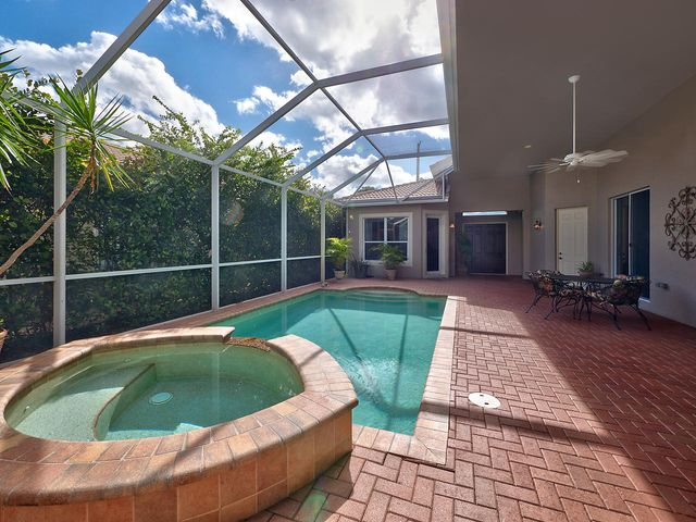 Expansive Resort style pool and spa with covered screen and pavers great for entertaining