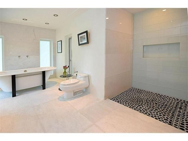 """shower has marble and glass walls and rain shower head, 24""""x 48"""" textured marble on floors and walls"""