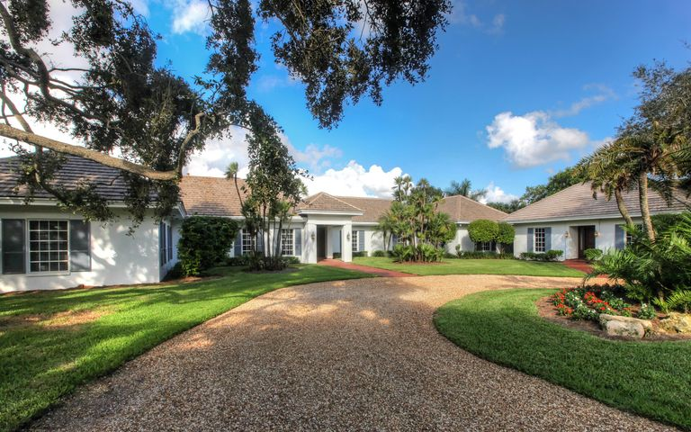 Sited on almost 2 acres with long winding driveway through mature majestic trees and tropical foliage.