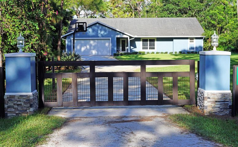 Beautiful front gate and paved driveway.