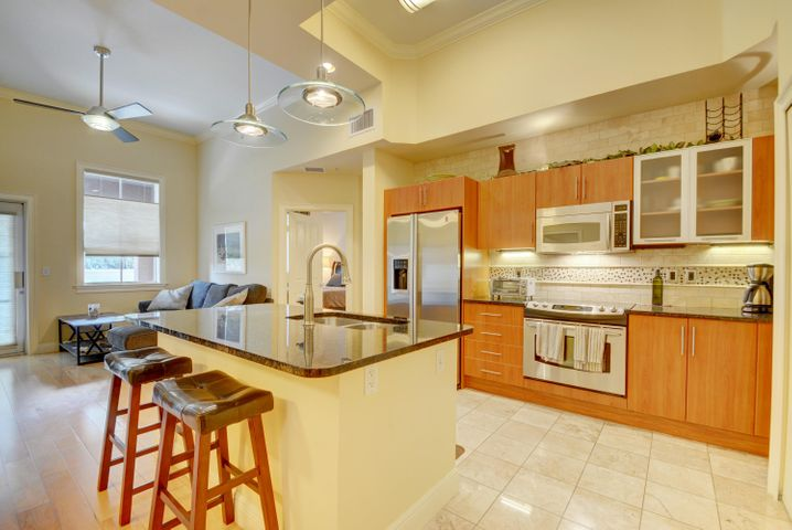 Beautifully updated great room with large island. Real wood floors throughout the great room and marble in the kitchen. Custom lighting and backsplash in this large and open kitchen space which feels even larger with the 12 1/2 foot ceilings throughout.