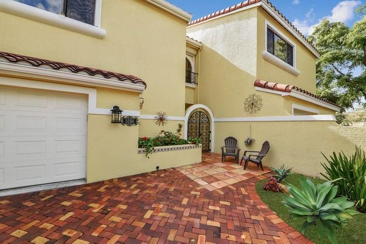 Large beautiful, newer pavered driveway with a one car garage and an arched gated courtyard entrance.