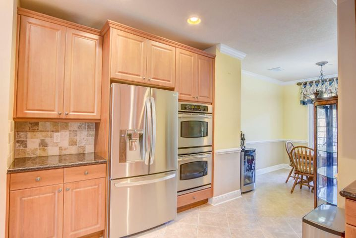 Gourmet kitchen with stainless steel appliances, gas range, double ovens, breakfast bar and dining area