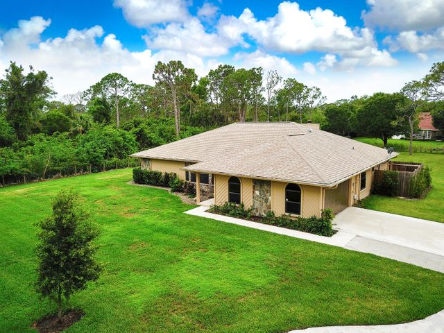 Completely Renovated Beauty in sought after Jupiter Farms on over 1 Acre, located on a PAVED road. High and Dry Lot. Pine Trees.