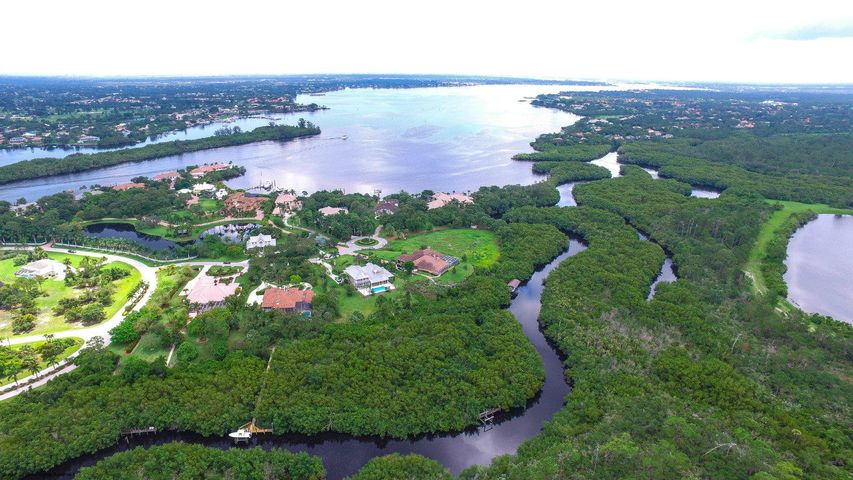 Discover this spectacular waterfront estate home on 2.48 acres backing to a nature preserve teeming with wildlife (Eagles, Blue Heron, Sandhill Cranes + more) located in the very private upscale community of Bay St. Lucie. Solid CBS construction on 1st floor, 2x8 construction (stronger than concrete) on 2nd floor + Hardiplank siding. Open plan living room with towering ceilings. Very spacious rooms, formal dining room, large media/game/family room or possible 5th bedroom on 2nd floor. Gourmet kitchen with granite countertops, SS appliances, 5 burner cooktop, wine cooler, solid wood cabinets, built-in desk + plenty of storage. Huge screened patio overlooks fenced in pool. Boardwalk leads to deep water ocean access dock for up to a 50 foot boat + 11,000# lift. Summer kitchen.