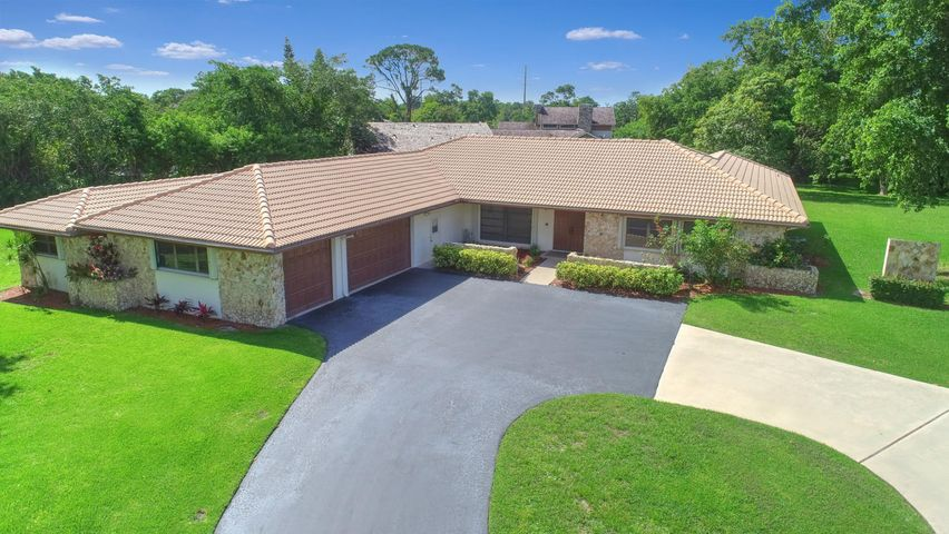 """Are you a car collector/restorer, boater, woodworker or all around hobbyist? Do you LOVE to garden? Do you dream of having your own Family Compound? If you said YES to any or all of this, then this is the property for YOU! On 2.45 acres at the end of a culdesac on the most desirable street in Ponderosa, sits a spacious pool home w/3 car garage PLUS a 40'x24' separate building to easily house an RV, several cars or boats or anything else you can think of! Additionally, there is a 460 sq.ft. building for a separate workshop PLUS another 300 sq.ft. hobby/storage area. OR,Property has the potential to be subdivided into two,separate, acre+ lots. Main home is most popular Commodore model with formal Living & Dining Rooms plus a spacious eat-in kitchen w/separate family room. Screened pool. ANSWERS TO FREQUENTLY ASKED QUESTIONS:  * Roof installed 2002 * 2 Zone AC - Living Area 2011. Bedrooms 2015 * 2 water heaters - not certain of age * Storm protection - Accordion shutters except front door which is panels * Sprinklers are on a well for LOW water bills * RV Building on 2nd lot is 16' high. Dimensions 40' x 24' PERFECT for boats, cars, camper, or an RV! * Storage building adjacent to home is 11'4"""" x 40'4"""".  Makes a great workshop or boat storage * 3 car garage PLUS another (yes another!!) workshop attached to home.  * Beautiful fruit trees: Mango, avocado, banana *  HOA fees are paid on 2 lots.  Includes security patrol, street lights, parks, tennis, fishing pier, jogging/bike trails and maintenance of all common areas. *  """"A"""" rated neighborhood schools:  Waters Edge Elementary, Loggers Run Middle and W. Boca High Schools * Neighborhood shopping is walking/biking distance. Publix, Walgreens, nail and hair salons, Sherwin Williams, Subway, Wendy's, Dunkin' Donuts, restaurants, dry cleaners and more. *  Just minutes from South County Regional Park and Amphitheater where you have:  Water Park, Doggie Park, more tennis, nature trails, tot lots, ball fields, golf and more!"""