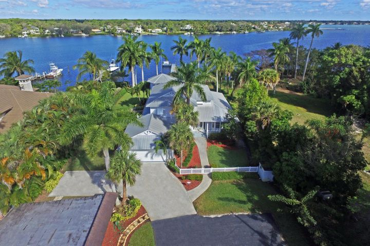 Key West style with old Florida charm! Enjoy wide, water views of the wild and scenic Loxahatchee River from this 3BR plus den/3BA home, situated on a 3/4 acre home site! Features include a small 1 bedroom guesthouse, pool and private dock. Straight shot to the Jupiter Inlet by boat!