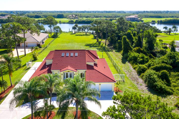 Set in the 97 acre Spruce Bluff Preserve in a secluded gated community on the North Fork of the St Lucie River w/ ocean access, this well loved 5 bedroom 4 bath, 3700+ sq ft home on an acre lot is ready for a new owner. One of a kind - from the dramatic entrance to the boat dock at the end of the fenced acre lot, the possibilities abound. Four bedrooms 3 full baths, & loads of living space on the first floor, & an expansive master suite with balcony on the second. Screened porch & open 9' deep salt water pool. The house has accordion shutters, dual zoned A/C, 500 gallon owned in ground propane tank, new metal roof, fresh paint in and out, new washer/dryer, new toilets, new sprinkler &  jacuzzi pumps. Dock with electric & water, 2 slips with lifts. Low HOA. 2 car garage, with