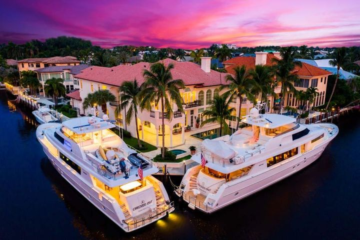 Located on a point lot with over 240 feet of Intracoastal waterfrontage, 1003 Rhodes Villa Avenue offers exceptional South Florida luxury living. Boasting over 11,300 total square feet, the six bedroom residence is tucked away at the end of a quiet cul-de-sac one block from the beach and about a mile from the shops and restaurants of Atlantic Avenue. Serious boaters will appreciate the Intracoastal waterfrontage in a no-wake zone with expansive private dock for multiple yachts and boats. Features include formal living and dining rooms; theater; large kitchen; loft; walls of French doors and windows overlooking the pool, grounds and Intracoastal; balconies; covered loggia with summer kitchen; four-car garage and elevator. Enjoy the beach area in this rare point lot waterfront estate. Distinguished with an East Delray Beach address, this property is complimented by the impressive point lot with 243 feet of Intracoastal waterfrontage in a no-wake zone and two nearby inlets for ocean access. Enjoy the beach just one block to the east and the boutiques and eateries of East Atlantic Avenue just over a mile to the north. Plan outings to Palm Beach, Boca Raton and Fort Lauderdale along scenic A1A. Travel is easy with several private jetports and three international airports accessible via Federal Highway or Interstate 95.  This beach area estate is the quintessential home for entertaining with spacious living areas, abundant parking, full bar and extensive wine room for social gatherings. The decorative brick driveway provides ample parking for residents and guests alike and leads to the stately portico entry. The foyer unveils the first glimpse of the interior with its soaring and detailed ceilings; Turkish marble floors; custom molding and oversized baseboards; and floor to ceiling wall of windows and French doors providing stunning views of the pool and Intracoastal Waterway beyond. The formal living room has an ornamental ceiling two stories above, stone fireplace, thre