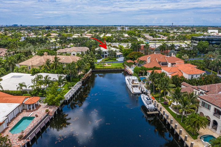 Most desirable waterview home in The Sanctuary, across from the deepwater canal offering beautiful water views. This unique home sits on a 14,000+ sq ft lot featuring a private tropical backyard with a pool/spa and outdoor living/entertaining spaces. Have a boat? Take advantage of the extremely affordable 21 slip marina located within this luxury community. The home features 5 bedrooms, a library/den/music room, loft, and media room (one bedroom used as maids quarters or mother-in-law suite). The Great Room has soaring ceilings, stone fireplace, wet bar and media room - perfect for entertaining! Floor to ceiling glass windows overlook the waterway in the front and the pool in the back. The open loft on the second level overlooks the ground floor and features space for a billiards table and wet bar. The Master Suite offers dual walk-in closets as well as a sizable bathroom with his and her showers and sinks. This home is ready for you to update and make your own - great floor plan flows well and just needs your personal touches! The Sanctuary is one of the finest private gated waterfront communities in Florida, with a 20 slip boat marina, 24/7 security and water patrol, playground, basketball court, and two Har-Tru tennis courts. The community's affordable boat slips can accommodate a 75 foot yacht. Close to Boca Raton's finest shopping and dining, minutes to the beautiful beaches and highway access.