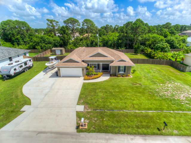 """A Rare Find! This custom built Gem Builder ''Marquis'' model located in the middle of just under a half acre of land has it all. Bring the boat, camper, and other toys with parking for all on the 20ft wide extended driveway. The home was just painted inside and out, has a brand new 15 seer Rheem A/C system, 2016 built 17'x34' saltwater pool with a variable speed pump, sun shelf, seating, and automatic vacuum. The hotwater heater was also replaced in 2016. Mature landscaping, decorative front covered porch, double door entry, plantation shutters, transom windows, and the vaulted ceilings make for a welcoming entrance. Inside you will find Bamboo flooring, upgraded granite countertops, stainless steel appliances and a gas range. The home is fully fenced and has gutters. Propane tank is lease A Rare Find! This custom built Gem Builder """"Marquis"""" model located in the middle of just under a half acre of land has it all. Bring the boat, camper, and other toys with parking for all on the 20ft wide extended driveway. The home was just painted inside and out, has a brand new 15 seer Rheem A/C system, 2016 built 17'x34' saltwater pool with a variable speed pump, sun shelf, seating, and automatic vacuum. The gas hotwater heater was also replaced in 2016. Mature landscaping, decorative front covered porch, double door entry, plantation shutters, transom windows, and the vaulted ceilings make for a welcoming entrance. Inside you will find newer Bamboo flooring, upgraded granite countertops, stainless steel appliances and a gas range. The floor plan is perfect for entertaining and wraps around the pool. A separate 4th bedroom and 3rd bath are split from the other 2 bedrooms. The outdoor living area features newer """"palm"""" fans, mature Areca palms, and is fully fenced. There is also gutters around the whole home. The 16x10 shed is perfect for seasonal storage and has power. The propane tank is maintained and leased by Amerigas. The property is a short bike ride to the new Woodland Tr"""