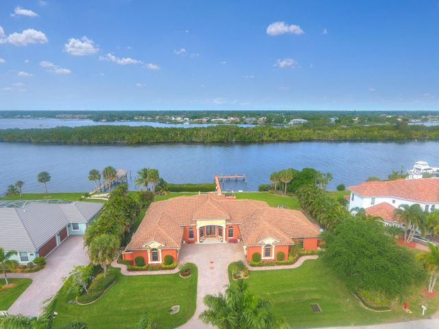 This stunning Riverfront home is perfectly designed to capture wide water views from most rooms and utilize the full 150ft of shoreline of the North Fork of the St. Lucie River. Solid built construction by Gulick Construction company, one of the areas prominent custom builders in 2011, designed to adhere to all current Building codes with Impact Glass doors and windows, High-end finishes with cast stone accents, hardwood cabinets, custom moldings, 4 car garage plus AC wood shop, 4 BR, 4 BA, office, Formal living & dining rooms, informal Family room with fireplace, open kitchen with center island, Gas cooktop, Solid cherry cabinets, walk-in pantry, whole house generator with 1,000gal propane tank, roof top deck, dock (8ft low tide), no fixed bridges for large yachts or Sailboats Owner Financing available to qualified buyers!