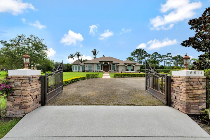 Rare estate home on a paved road in Jupiter Farms! All you'd expect in a fine residence in the Farms on over an acre of landscaped countryside is here! Open the double doors to professionally applied venetian plaster walls, custom artwork in the trey ceilings, soaring 12' lofted ceilings & 16' vaulted pecky cypress ceilings in living room. Experience the ambiance of the family room fireplace & the soft glow of the gas lit mantel or enjoy a home cooked meal prepared from the large gas range while lost in thought gazing at the flickering kitchen fireplace. Sleep in peace w/ the newly installed impact glass & premium exterior paint paired w/ a recently installed screened-in patio featuring travertine hardscape overlooking a beach entry pool w/spa/waterfall. Request Feature Sheet 4 all detail Benefit from the solar generation & generator for low utilities & backup power for essential circuits.  Desire space for a hobby or business? Then you'll appreciate the spacious garage/workshop built in 2010.  Invite guests or family over in their own finely appointed separate guest suite overlooking the pool.  Need privacy or a fully fenced yard?  Then you'll appreciate the two double gates on the circular driveway and complete fencing around the property. Love to have outdoor parties?  Enjoy grilling?  See pictures of the professional outdoor kitchen! Most appliances and equipment has been recently upgraded by new owners including the home air conditioning units.  Request the Feature Sheet for complete details!