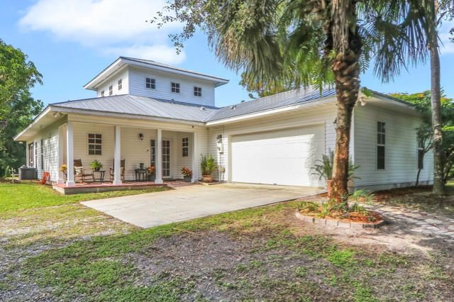 Come enjoy this Key West style home on a tranquil 1.25 acres in Jupiter Farms. The 20' ceilings, french doors, and open floor plan make for a comfortable living space with a ton of natural light. The master suite opens to the patio with bamboo flooring and beautifully renovated custom bathroom complete with oversized shower, jet tub, and walk in closet. Other features include laundry room with utility sink, oversized and air conditioned garage, newer water softener, and brand new AC. Enjoy the spectacular views of the backyard from the screened in patio. Plenty of room for a pool. Property includes a shed and several pads for parking your toys or recreational vehicles. Fully fenced and gated, and conveniently located close to Jupiter Farms Road.