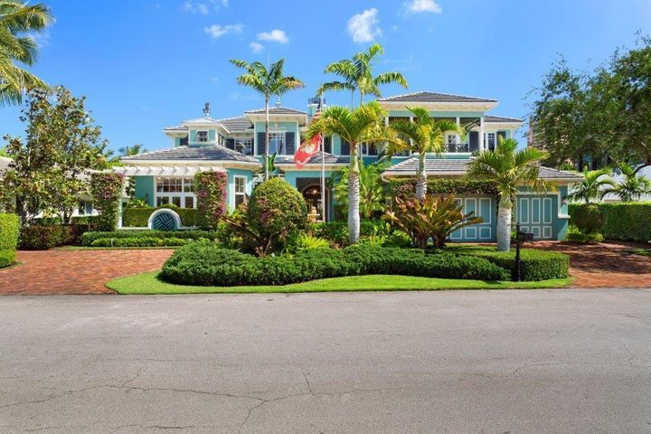 """Devoted to casual elegant resort living, this impressive British West Indies-inspired estate is secluded on manicured tropical grounds in the exclusive Royal Palm Yacht & CC. 2019 NEW METAL ROOF with solar panels to generate negative electric bills, 2016 five  new AC's.  Fine detailing and high standards of quality characterize this six-bedroom residence which has been scrupulously designed and constructed by a noted custom builder, of Qualk Homes, as his own private estate. Classic styling is given fresh modern appeal in the well-planned interiors which flow openly and spaciously, easily transitioning from formal to casual settings.  Rich cherry floors add grounding warmth to the airy atmosphere below soaring ceilings detailed with architectural treatments.  Fireplaces appoint the dramatic two-story living room and cathedral-ceilinged family room, also the resort-style outdoor entertainment area, accessed from the living areas as well as the first-floor grand master suite.  Verdant tropical landscaping and fairway vistas across Thatch Palm Drive complete this picture-perfect estate in world-class Royal Palm.  Location Thatch Palm Drive, Boca Raton, Florida.  Boca Raton's prestigious signature address, Royal Palm Yacht & Country Club, offers guard-gated seclusion in a premier location across from the landmark Boca Raton Resort & Club and the Atlantic Ocean beach.  Mizner Park's world-class shopping and dining are close at hand, and Boca Raton's private executive airport is only about a 15-minute drive.  Property Built in 2007 by Qualk Homes, this British West Indies-inspired estate takes full advantage of its spacious and lushly landscaped grounds, also viewing the fairway across the street.  Tropical foliage secludes the expansive outdoor entertainment area.  Here, the wraparound loggia with gas fireplace and summer kitchen overlooks the resort-style pool with rock waterfall spa and """"beach"""" wading area.  Residence Beautiful custom millwork refines this spacious res"""
