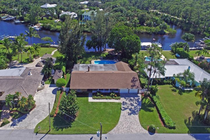 Great opportunity to own a Riverfront home with 100' of direct river frontage for under $1,000,000.  This charming 3BR/2Bth home sits on a large lot with wonderful, serene views of the Loxahatchee River and offers lush tropical landscaping and privacy galore.  The quiet street, pool, gazebo w/ sink & electric, dock and large covered patio w/ brick summer kitchen, make this the ideal home to entertain in, S. Florida style!  The interior of this clean/well keep home has a spacious formal living room with brand new carpet, formal dining room, spacious family room with fireplace and wet-bar, open kitchen overlooking the breakfast area, split bedroom plan and updated master bathroom.  If you're looking to be on the River and under $1,000,000, this home is for you!