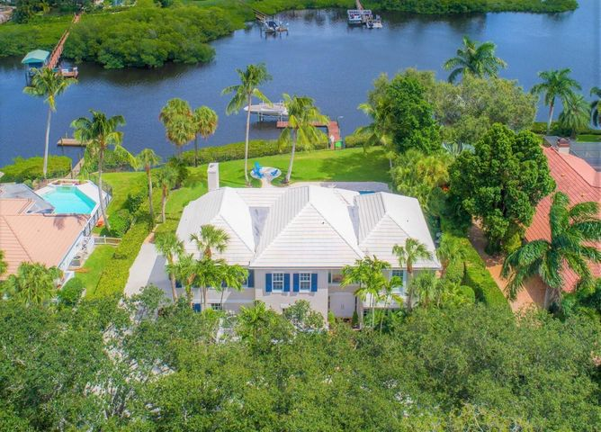 Spectacular riverfront home located on the North Fork of the Loxahatchee River on 1/2 acre + lot. This stunning pool home features 5 bedrooms, oversized loft, 4.1 baths & 2 car garage with over 4800 sq ft. SOLID built 2 story CBS home featuring ALL IMPACT DOORS & WINDOWS, hurricane rated newer roof, and foam/icynene insulation for extra stability & high efficiency. Impeccably maintained by the owner, the newly renovated upgrades include: custom island kitchen with custom white cabinetry with soft close, mitered 6cm quartz counter tops, custom tile back splash, farmers sink and stainless steel appliances; newly stained wood flooring throughout, new dock w/ electric & water, new 12K lb boat lift, 2 new 5-Ton AC units, new travertine marble patios, house generator .... & dedicated buried propane tank,  whole home water filtration system, remodeled 2nd bathroom & powder room, new washer & dryer, new interior/exterior paint, & new landscaping. The Chicago brick drive & walkway lead into a grand 2 story foyer.  Formal living & dining room are beautifully finished with River views & French door leading to a side patio & private fountain. First floor den/office features French door entry to front patio.  The 2 story family room features a fireplace & is overlooked by the open loft, all featuring river views. First floor guest suite, mud room & finished laundry room. The spacious master suite features sitting area, double walk-in closets, dual vanities, & double shower with rainfall shower. Beyond the large newly remodeled screened patio, the lushly landscaped yard features a custom salt water pool with travertine marble decking, fountain features & new pump. The private gated community of Heritage Oaks features a spectacular oak canopy though out the private roads, as well as a world class tennis facility & clubhouse.  This amazing community is truly one of a kind, off the beaten path, but close to everything!!