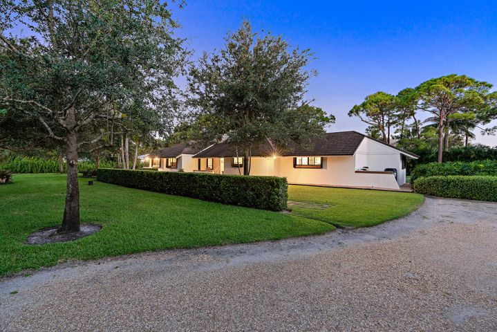 IMPECCABLE single-story CBS (concrete block construction) pool home located off the highly sought after Loxahatchee River Road! Situated on 1 FULL ACRE of land (!!!) and with a brand new pool, 50 year+ metal roof, lush custom landscaping, and impact windows, this home will check every single box of your search criteria and more! 6422 Fox Run Circle will sweep you off your feet from the moment you set foot on the HUGE property and enter the home's front door! Enjoy an expansive open layout with vaulted ceilings, charming wood beams and millwork, beautiful 20 inch Coquina coral tile flooring throughout, and a real coral stone fireplace. You will love the newly renovated modern kitchen featuring gorgeous tile backsplash, executive cabinetry, quartzite countertops, and [click to read more]   Kenmore Pro double ovens. This custom chef's kitchen boasts ample storage and space with a spacious pantry and a cook island.  ---  Retreat to your master bedroom to find a sprawling suite with soaring ceilings complemented by wooden beams, and an ensuite with a custom, real wood vanity, a frameless shower, and a linen closet.  ---  The backyard at 6422 is the perfect place to relax and enjoy the South Florida tropical climate with a new sparkling, salt-water swimming pool with lights and PebbleTec completed in 2017 by RHR pools. With its extensive, lush landscaping with clusia and areca palm trees, fountains and custom cabana bath with a walk-in shower, you'll want to spend every moment in your backyard soaking up the sun and hosting friends and family for pool days and barbecues.  ---  Other features you will love about this home are the huge laundry room, extensive closet space, a spacious two-car garage and 400 Amp Service Panel for electric. This home has a $45k stone-coated metal roof from 2012 with a 50-year warranty. The 2 ACs are from 2014 and are under a 10-year warranty and its 2 tankless electric water heaters are also from 2014. The home is on well water and a water sof