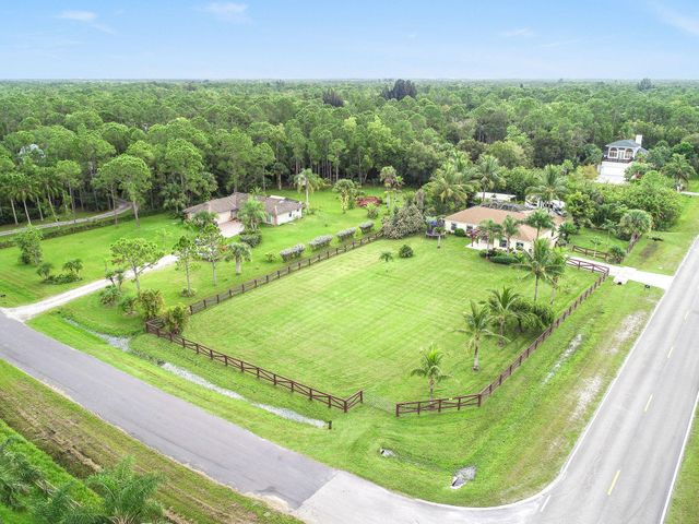 Jupiter Farms Living at its Finest! Paved road and CBS construction in Jupiter Farms - yes! Relax in this 2,500+ sq ft, 3BD, 2BA pool home on a fully fenced lot (just under 1 acre). Beautifully landscaped, and on a corner lot.  This home has more bonus features than your average house, including an oversized den off the kitchen with a trendy Dutch door (which is a MUST if you have little ones) and a garage conversion that includes a 400+ sq ft flex room, perfect for that exercise room or extra bedroom. The home offers an open concept where you can enjoy the kitchen, living, and dining all from one room. The kitchen features newer stainless appliances with premium quartzite countertops. Upgraded wood-like tile flooring in the main living area. Other features include a screened lanai off the pool area with glass windows on the east side for extra added protection from the elements. Add to all of these benefits a 2018 whole house generator with a buried 500 gallon propane tank. The home also has a detached workshop with a covered pad for your boat or that special car.  More importantly, there are TWO entrances to the property, the main paved driveway or the back entrance which is perfect for your RV or boat! Conveniently located only 5 minutes to the JF Publix and 10 minutes to the FL Turnpike and I-95. Well respected, this home delivers!