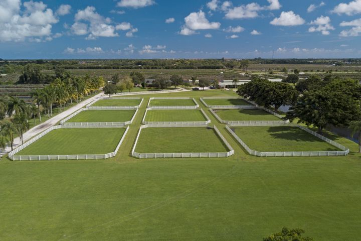 17 Acre Equestrian Training Facility in Delray Beach. Coral ''C'' Stables is a turn key, fully functional and operating 25 stall show barn with every conceivable amenity available. The  residence, is a picturesque two story three-bedroom lodge with a wraparound covered veranda overlooking the estate grounds. There are two separate grooms/staff quarters  as well. One covered 225 X 95 mirrored arena with GGT footing and one 250 X 150 open arena. Six 120 X 90 irrigated paddocks. Owner's office, tack room, feed and 3 additional equipment storage buildings, 4 wash stalls and laundry room. This property is extremely peaceful and secluded yet convenient and secure with the opportunity to build a substantial home . 13 Miles to the P.B. International Equestrian Center and only 8 miles to the beach.