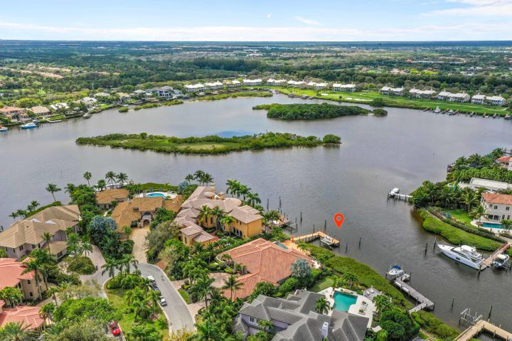 Spectacular views across the widest waterway within Admirals Cove, this single story 4280 sq ft gem delivers breathtaking views to all primary rooms. 3 large bedrooms, 3.2 bathroom, office/den, family room, 3 car garage. One of a kind location on a quiet clubhouse de sac of Commodore drive, close to clubhouse. Island kitchen leads to family room, marble and wood floors, new master bath, light and bright, generator. Get ready for entertaining with large deck and sundeck, summer kitchen, freeform vanishing edge pool, hot tub, room for 70 boat, and additional boat on lift. Required golf membership purchase conveys all the first class amenities of Admirals Cove including two spectacular clubhouses, 45 holes of golf, 5 restaurants, 63 slip brand new marina with floating docks, Yacht Club, 13 har tru tennis courts, state of the art fitness, brand new spa, Covesters kids club and Platinum service.