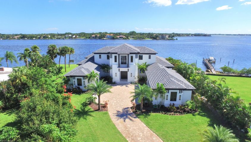 This beautiful, contemporary British West Indies home built in 2016, is located on the widest part of the Loxahatchee River and is filled with modern flair and luxury finishes throughout. The 4 BR/4.5Bth/4-car garage home, with study/office and exercise rooms, is located on a quiet street and offers wide/panoramic water views. Enter through a dramatic foyer and behold the stunning water views surrounding the formal living room with custom ceiling and linear gas fireplace. A luxury chandelier hangs from a custom ceiling and dazzles your guest in the waterfront formal dining room. The chef's kitchen is a stunning place to gather and comes equipped with a large prep island, custom cabinetry, quartz countertops, walk in pantry and top of the line stainless steel appliances, including Thermador six-burner gas cooktop, dual ovens, microwave and Sub-Zero refrigerator.  The spacious family room comes equipped with two sets of pocket sliding doors that open up to the patio/pool area. The first floor master suite offers a dramatic master bathroom and enormous walk-in closet.  A beautiful staircase leads to a second floor family room with wet-bar, balcony and two large en suite bedrooms. Additional interior features include marble and hardwood floors, designer fixtures, elevator, state of the art security system and hurricane windows and doors throughout.  The exterior features of the home include a gated entrance, decorative paver driveway, lush tropical landscaping, large covered patio with summer kitchen, vanishing edge heated pool, seawall, dock and approximately 200' of river frontage.