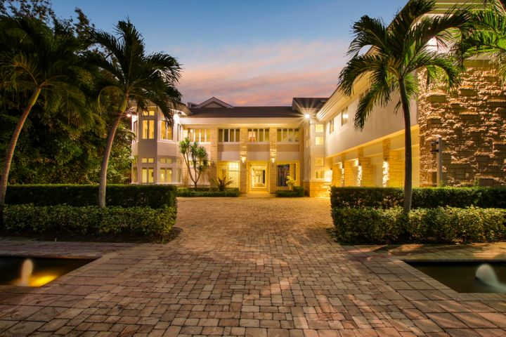 Impressive direct intracoastal estate boasting over 10,000 living square feet. This private, gated, courtyard-style home offers soaring ceilings & plenty of architectural details. Open floor plan with lots of natural light, stone fireplace, & breathtaking water views. Large chef-friendly kitchen, freshly painted inside & out with new carpeting & impact glass windows throughout. Oversized pool with spa & fountains, brick paver patio, & built-in summer kitchen. Ultra-private lot with over 100 ft of water frontage on a wide section of the intracoastal with extensive landscaping, 30+ palm trees, winding driveway, private boat dock with 40,000 lb lift, & no fixed bridges. 2BR/3BA guest house with a kitchenette is attached to the home via breezeway above the home's four-car garage.