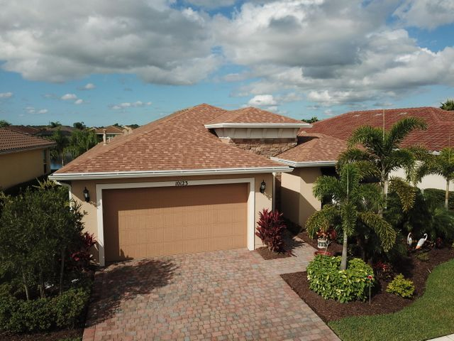 Come see this gorgeous Lauderdale model in beautiful, vibrant, 55+ Vitalia at Tradition. With 2 beds, 2 full baths, a unique half bath, den, and beautiful lake view, this home is a must see. Fall in love with the tile floors throughout, French doors into the den, stainless steel appliances, granite countertops, gas range, huge cook's island, and the largest screened lanai available in Vitalia. Other features include impact glass windows and doors, a rare extended garage, tiled backsplash, fresh paint, ceiling fans,  and much more! Enjoy Vitalia's 24,000 s.f. clubhouse with tennis, pickleball, bocce, resort style pool and spa, grand clubhouse with professional entertainment and much more. Come join the fun!