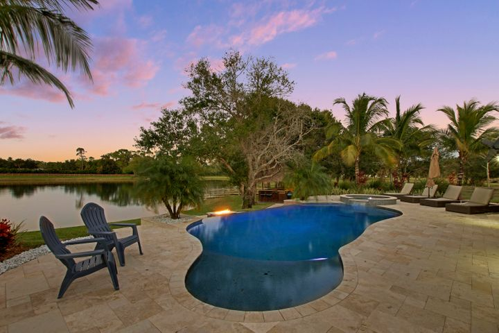 Interested in living on your own piece of paradise, surrounded by 12 acres of privacy and quiet, yet minutes from all conveniences and the stunning Jupiter beaches? Don't miss this rare property. Custom built home with 5 bedrooms, 3 full baths, plus den, open gourmet kitchen/living/dining areas, plus separate sun filled guest house w/ living/dining area, bedroom & beautiful bath. Stunning nature views and impact glass throughout. Exceptional outdoor living & entertaining with infinity pool, spa, fire pit, tiki hut w/ outdoor kitchen. Bring your family, animals, boat, cars, toys! Set up a workshop in your brand new 20x35 metal building. Gated, landscaped entryway w/ meandering paved driveway & fenced pastures. Well priced for this incredible property.