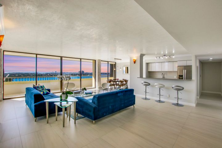 Enjoy wide open water views of the Atlantic ocean, Singer Island shoreline and the whole Intracoastal Waterway! This open concept condo has been renovated top to bottom from the studs out. Ceilings raised and a Venetian plaster coating added to create a brilliant high shine. This one of a kind condo features 24'' x 48'' Italian porcelain tile throughout and extends onto the balcony creating an amazing outdoor living space. The open concept layout is perfect for entertaining or relaxing at home watching the sunset. The designer kitchen features extensive custom cabinetry, pantry, an island with seating, quartz countertops, all new appliances and bar with wine fridge. The bathrooms offer beautiful tiled showers with luxury rainfall shower heads, frameless glass and double sinks with ... ... Quartz counter tops. The oversized laundry room features side by side washer and dryer with tons of extra storage space. There is also a bonus room which is perfect for a home office or additional storage. This pristine unit also features solid core doors, built in closet cabinetry, custom lighting and concealed sprinklers. Garage parking for 2 cars. The Reaches common areas have undergone extensive renovations including a brand new stunning lobby, waiting area (with TV & Library), mail room, gym and social/party room (with 3 big TV screens, new Pizza Oven, many gathering areas as well as counter style eating areas.) with lots of glass overlooking the ocean. The huge (almost 1 acre in size!) pool area has new furniture and there is also deck furniture placed at the beach, so owners do not have to carry their own chairs, if they don't wish to (there is a room for storing beach chairs). There is a lighted tennis court, a one-of-a-kind indoor racquetball court with viewing area, 2 shuffle board courts and indoor pool table. The building has CCTV in various areas, as well as 24/7 security gate attendants and call box at lobby entrance. Reaches consists of 94 condominiums (6 per floor) 