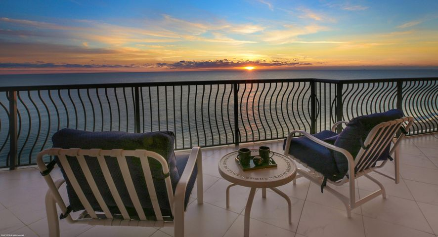"This is that very rare home on Singer Island with full balconies directly facing both the Atlantic surf and the Lake Worth Lagoon and Intracoastal Waterway.  If the afternoon sun is baking the west side and you want to relax in shade, head for your ocean balconies!  If the air isn't moving on one side and you want a breeze, just try another balcony - there's almost always a breeze somewhere in this wonderful 14th floor sky home.  Most floors in Via Delfino have only two units, and several floors contain full-floor condos  (there are only 33 units in the building, so there's a nice sense of community among your neighbors here).  This home is on the quieter, north end of Singer Island. This home is on the quieter, north end of Singer Island.  If you want a bustling ""resort"" atmosphere, this probably isn't a good fit for you.  If you prefer the ""private villa"" feel, this is your place. The unit has crown molding and Greek Tazzo flooring throughout, with cherry wood flooring in the master bedroom and granite flooring in the eat-in kitchen (with cherry cabinetry and matching granite countertops).  The eat-in kitchen includes a breakfast nook with its own ""Juliet"" balcony looking to the north.  Combined with the other balconies, this provides a more than 270 degree view. The unit includes two deeded spaces on the second level of the parking garage.  There's direct beach access from that level, complementing the geothermally heated swimming pool, spa, owners' cabanas and outdoor BBQ area.  The oceanfront master suite is breathtaking, with his/hers bathrooms (guess which one is bigger and nicer, with a jetted Roman tub), two water closets and a shared, walk-through shower.  There are five bathrooms in the unit.  A third bedroom has custom-designed a built-in desk, cabinets and shelves so it doubles as an office with a Murphy bed.  Built-in refrigerated wine storage and wet bar in the living room.  Full laundry room with nearly-new washer/dryer.  Two pets are allowed, and there is an outdoor dog area on the grounds.  The building offers a fitness center and library on the ground floor, along with guest suites available for rent at nominal cost when you have more guests than beds and that can be a ""problem"" in this idyllic setting.  Palm Beach Gardens is five minutes away, and it's 20 minutes to West Palm Beach and PBI airport.  Built in 2003, Via Delfino has a full-time residential building manager, gated entrance, fitness center and library. You cannot find comparably priced homes on Singer Island with the dual east/west balconies.  That's just one of many features making #1401 Via Delfino a Singer Island jewel."