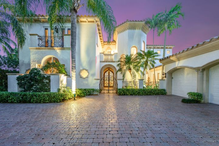 Located behind the private gates of the award winning Loxahatchee Club in Jupiter Florida, this pristine estate is located on a private cul-de-sac on approximately 1/2 lake front acre with stunning panoramic views of the lake and Jack Nicklaus Signature golf course. This updated home was designed and built with impressive details such as high-beamed ceilings, French doors, carved mantelpieces, and exquisite cabinetry. The home's open plan and indoor-outdoor flow allow for both luxurious intimacy and large gatherings. Arched windows and doorways provide stunning sightlines. The living room, family room, and chef inspired kitchen offer gorgeous views and direct access to the pool terrace through French doors. The luxurious master suite has his and hers baths, spacious closets, and private gym overlooking the lake and golf vistas. Additional features include a formal dining room, 3 large guest bedrooms each with en-suite bathrooms, entertainment loft overlooking lake and golf course, and custom wood paneled library/study with private balcony. This property is professionally landscaped and includes infinity pool, outdoor kitchen, and fire place. The garage provides space for 2 cars and a golf cart.