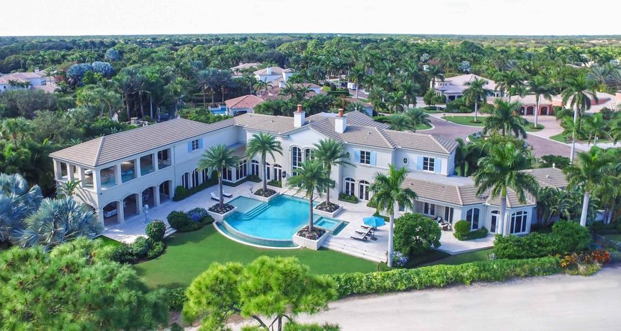 Exceptional views from this custom estate home situated on the finest lot in prestigious Old Palm. Stately and elegant, this thoughtfully designed home exhibits glamour and luxury, built with the finest finishes. Spaciously designed with great attention to detail, 6 bedrooms, 8 fulls baths, 1 powder room, a library, and a theater comprise this masterpiece. The Master Suite is fit for royalty with two grand baths and two room size walk-in closets. Guests will enjoy their upstairs retreat with a private living area and balcony that boasts extraordinary views. The outdoor living space is resort like with its infinity pool, outdoor fireplace and fabulous lounging areas.