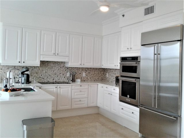 Spectacular updated kitchen with white stone counter tops and custom backsplash, new stainless steel appliances, and view to the serene Toscana grounds.