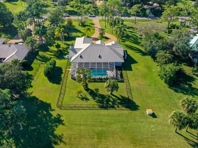 Stunning CBS pool home on 1 private acre w/standing seam metal roof on the C-23 canal! Large circular drive welcomes you to your freshly painted home w/impact windows & doors throughout! Spacious living room w/soaring vaulted ceiling overlooking the screened-in heated pool & spa for hours of family enjoyment! Beautiful kitchen with S/S appliances, snack bar & breakfast area, all w/magnificent views of the pool & manicured yard beyond. Enjoy the gas fireplace in the adjoining family room w/pocket sliders leading to your covered patio w/tongue & grove ceiling. Easy access from master bedroom to pool/patio. Luxurious master ensuite w/dual sinks, frameless shower & whirlpool spa tub for pure relaxation. Tile floors in main living areas & beautiful wood plank in BR's. Whole house generator!