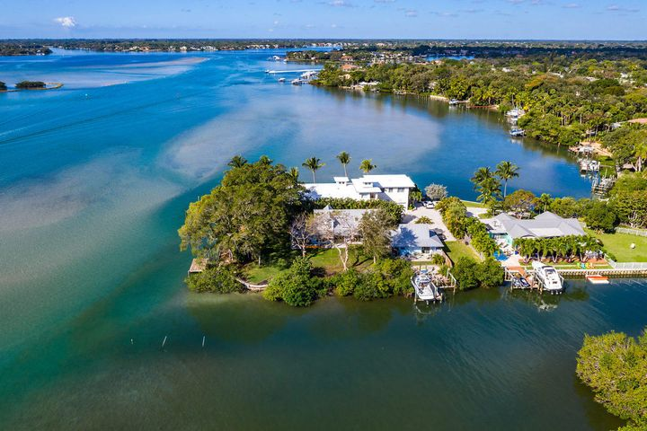 Incredible water views and the best sunset in Palm Beach County! This adorable property juts out from Riverside Drive into deep water of the Loxahatchee River and gives you direct access to the Intracoastal Waterway and the ocean via the Jupiter Inlet and has 280 feet of deep waterfront. Located on what was originally an island and now home to three unique properties with a shared driveway, This home is situated on 0.56 acres and the property consists of a main house and an attached guest / in-law apartment and garage. Boat dock was added in 1996 and boat lift added in 2009. This CBS 4 bedroom, 3 bathroom house retains its original character and charm as it was built as a fisherman's house and is surrounded by mature trees, a floating dock, fixed deck overlooking the water - and a waterside tree house!  Nothing else like it on the market in Jupiter.