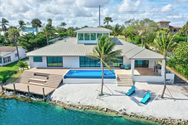 OPEN SATURDAY 2/22 FROM 1-3 pm. The Jewel of Juno on Ocean Dr! Your dream resort setting! Enjoy peaceful wide water and nature views plus cool ocean breezes! Steps to your own whitesand beach w/coconut palms, huge 30 ft dock for 15 ft boat & fishing! CBS construction, 4 BR/office, hurricane impact windows & doors, natural gas hi-end appliances, oversized quartzite island, cabinets galore! Open floor plan w/over 50 ft of glass sliders, heated infinity pool, spa and lake! 26 ft ceilings in living room welcomes natural light and blue sky's into your life! Over 4000 SF in one story. Large bedrooms each w en suite artistic full baths. Huge covered patio with outdoor kitchen. Enjoy shaded afternoon relaxation & entertainment, cooler morning sun. Walk around lake to access Atlantic ocean beaches!