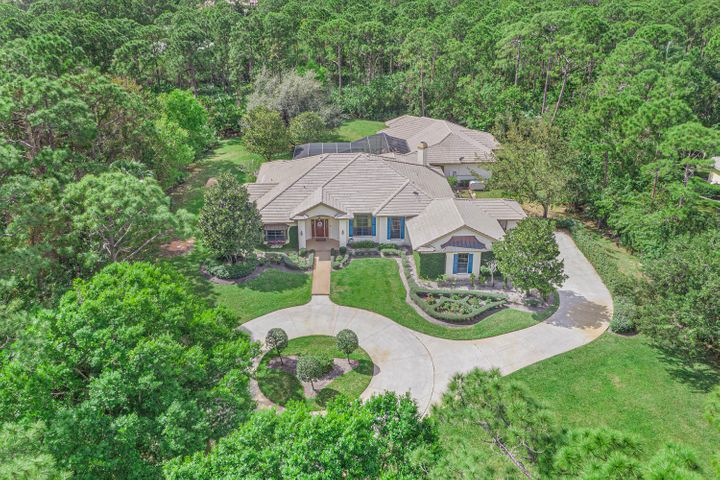 This exceptional home with vintage charm exists in the desirable Sabal Creek Community of PGA Village. The circular driveway invites you onto a lush and private 1.6 acres. The custom built home expands 5500 sq feet and is filled with an abundance of natural light.  French doors,  large screened back porch with pool and spa and  full summer kitchen are all ready for your outdoor entertainment. For wine connoisseurs there's a temperature controlled wine room with storage beyond your imagination for those special vintage labels. In addition to all of this there is a West Wing with a separate entrance perfect for an  in- law or guest quarters with a game room,  full bar w/ granite and upgraded appliances, living room, and a large bedroom with full bathroom. Located in PGA Village with low HOA Fee's there is a Manned gate for security, cable, common grounds & The Island Club offering something for everyone. Beautiful clubhouse includes fitness center, basketball, resort style pool,  tennis,  exercise room, ballroom, library, billiards, craft room, card room, entertainment, clubs & even travel. PGA Village has 3 Champion Golf courses open to the public and several different memberships are available plus the private Legacy Golf Course. Only minutes from St Lucie West where you can find New Restaurants, shopping, movies, bowling & even home of the NY Mets Spring Training. The Treasure Coast has amazing waterways for boating, fishing & beaches and located only 50 minutes from Palm Beach Airport and 1.5 hours to Orlando. With a perfect location the weather is beautiful all year round!