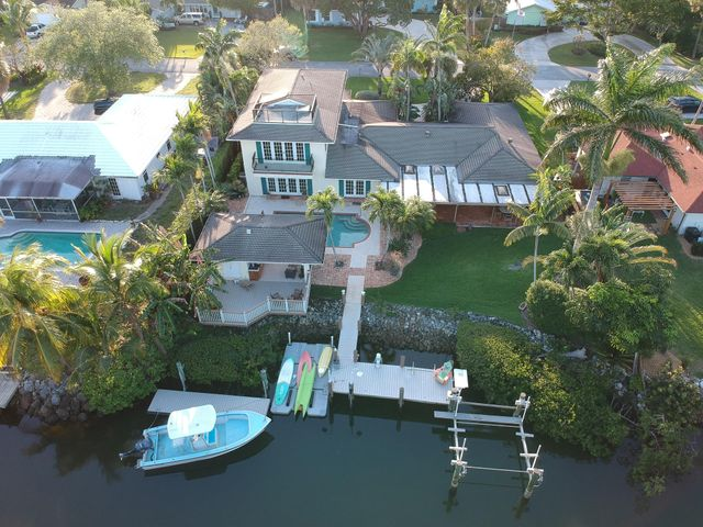 There is room for everyone in this 5 Bedroom, 4.5 bath Jupiter waterfront home! Great for entertaining guests with two boat slips and a top of the line boat lift, a summer kitchen and a 3rd floor viewing deck. A fully fenced in yard, convenient cabana bath, and quiet street allow for maximum family fun and minimum stress. Location is everything! This home is located seconds from the inlet, Jupiter Sandbar, and great restaurants. Updated kitchen, modern appliances, 16,000 pound Deco Boat lift, circular drive, plenty of room for kayaks, paddleboards or any watersports.