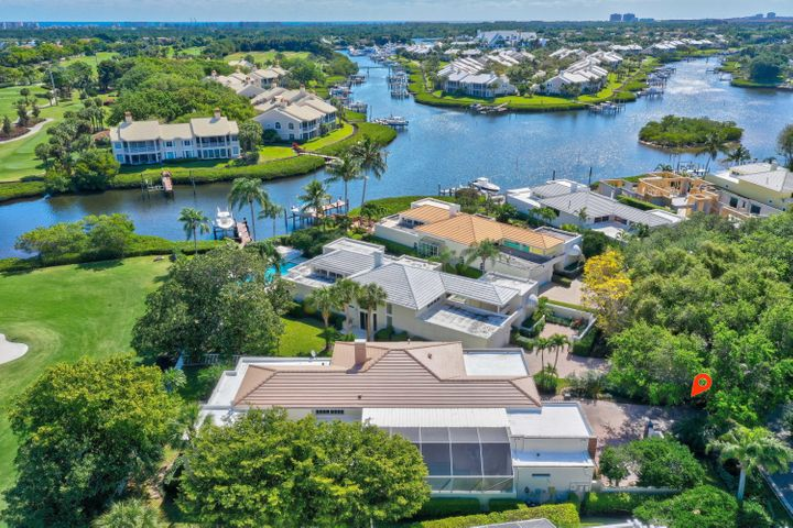 "When you think of Admirals Cove in Jupiter, Florida, you visualize emerald green fairways, pristine navigable waterways, luxury homes & amenities, and a social life that will never leave you wanting for more. You can live the lifestyle of your dreams here, at 118 Waters Edge. From the moment you drive down the oak canopied streets, you'll realize you've found something unlike other properties in this price range. The front elevation has been recently upgraded with a new contemporary look.  Layered stone, wood tile and Bahama shutters add a wonderful curb appeal that separates this stunner from the other homes on the street. Listen to the tranquil sounds of water cascading down the serene water fountain while sitting poolside in your oversized courtyard... This concrete block home features lush tropical landscaping, separate guest house and incredible views of the golf course and waterway.  Inside you will be overwhelmed by the large open spaces, granite and hardwood floors, solid core doors and a custom millwork package that includes applied moldings, crown moldings and 6"" baseboards throughout. Interior finishes include smooth textured walls & ceilings, two gas fireplaces (formal living and master suite) and a gourmet kitchen fit for a culinary chef featuring custom wood cabinetry, Sub Zero & Thermador appliances and granite countertops.  The master suite features a large sitting area, his & her bathrooms and a steam shower.  The garage was recently remodeled to make room for up to 4 cars, but the courtyard is really where the magic happens. Whether grilling steaks at the summer kitchen or swimming laps in the heated pool, entertaining your friends and family will be a delight when you call 118 Waters Edge home. This custom single family home may be one of the best home values in Admirals Cove."