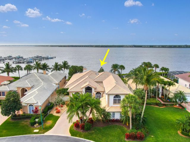 Talk about Value! You cannot imagine what an amazing house this is until you set foot in it! 5 bedrooms, 7 baths, 2 offices, both formal and family style living & dining rooms, summer kitchen, cabana bath, screened lanai with beautiful swimming pool and spa. ALL of it encompassing unparalleled views of the St. Lucie river at its widest point. Exquisite interior detailing includes opulent marble floors, high ceilings and lavish crown molding. There are 2 en-suite bedrooms upstairs occupying a versatile space that could easily become an in-law-suite, playroom or private Gym. Two car Garage plus golf cart parking and a deeded 40ft dock with a 9,000lb boat lift complete the package. Quietly elegant yet warm and inviting, nowhere else are you likely to find as much for the price.