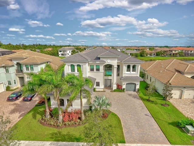 """Make sure to view BOTH Video & Virtual tours! Rarely available Designer Decorated ''Palermo'' Waterfront Estate! 6,171 A/C Liv. Sq. Ft., 7 Bed/6.5 Baths + 4CG. $290,349 in Upgrades and No Expense Spared! Quartz Kitchen with Artic white cabinetry, Center Island, Top Of Line 48'' Sub Zero refrigerator, Wolf gas cooktop, Double oven, 36'' SS exhaust hood! Polished Marble Flooring on 1st level & Solid Oak 2nd level, hallway & loft, Granite Wet Bar, Custom Window treatments & Light fixtures. Stunning Master suite offers built-out closet cabinetry, coffered ceiling, soaking tub, & spacious wrap around Veranda overlooking custom Pool/Spa/Patio & endless Lake views! Newest State-of-the-art security system from ''Vector.'' Security cameras installed in front & back of home, inside motions, thermostat, doorbell etc. Total Peace of mind and covered with secure monitoring by VECTOR Security Systems. Includes record capabilities to personal computer & phone app monitoring. Light, bright & airy situated in the exclusive ''PARKSIDE'' subdivision of Seven Bridges with 24/7 Manned Gated Security. Seven Bridges is the ultimate luxury community with 1st class amenities including a tremendous 30,000 square foot clubhouse that offers a fitness center, fitness studio, indoor sports court, card rooms, a game room, a multi-purpose room, saunas, lounge and 5-star restaurant! Soak up some sunshine at the resort style pool, spa or poolside bistro. Seven Bridges offers activities to keep the whole family happy and healthy with a basketball court, 12 Har-Tru tennis courts, an aqua lot and a shaded playground. Located close to shopping, dining, entertainment, """"A"""" rated schools, major highways and trendy Atlantic Ave."""