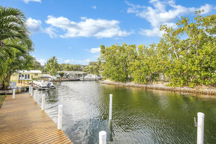 BRING YOUR BOAT UP TO 80 FEET!  This direct waterfront home in Pirates Cove has a dock that will accommodate an 80' boat, (no fixed bridges), private water views, gorgeous white porcelain tile throughout the living area, nice kitchen w/ updated cabinets, 3 bedrooms or 2 bedrooms and large media room, screened in salt water pool, patio gazebo, wood deck, cabana bath, 1 car garage, fenced yard, pet friendly. This home is 4 lots off the Intracoastal and is in a multi-million dollar neighborhood. Great location! Close to restaurants and shops on PGA and in the heart of Palm Beach Gardens. Landscaping and pool maintenance included in rent. Don't miss out on this rare waterfront home!